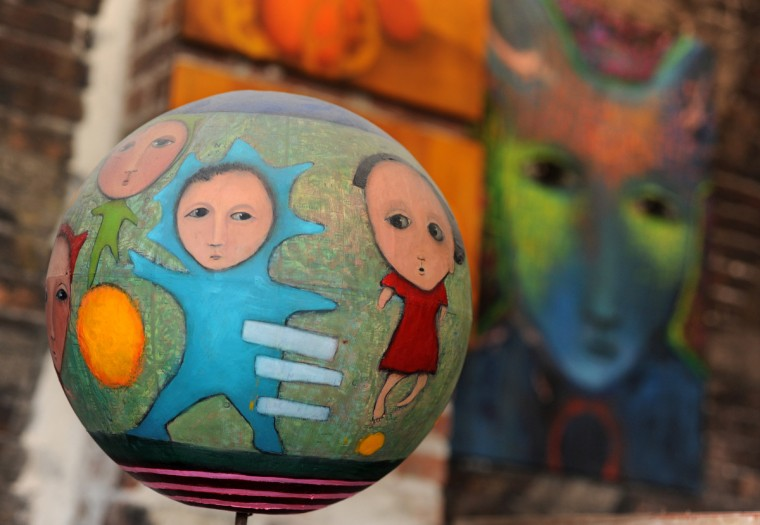 The globe in the foreground is part of a series titled, Childhood Dreams, Memories and Deja Vu, created by artist Lania D'Agostino of D'Agostino Studios. In the background is a painting froom her Jackrabbit series. (Algerina Perna/Baltimore Sun)