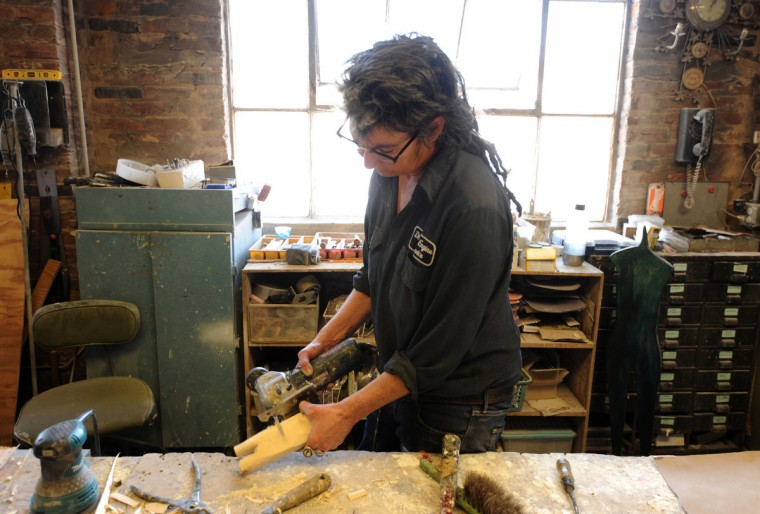 Artist Lania D'Agostino of uses a jig saw on a scrap of wood to create a female figure. She is pictured in her studio where she creates art including paintings, sculpture and life-cast figures. (Algerina Perna/Baltimore Sun)