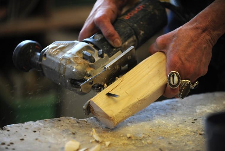 Artist Lania D'Agostino uses a jig saw on a scrap of wood to create a female figure. (Algerina Perna/Baltimore Sun)