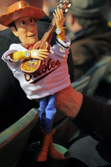 """Woody from the Toy Story movie franchise is held by George """"Birdman"""" Fuhrer of Clearwater Beach at the Baltimore Orioles' home opener at Oriole Park at Camden Yards. (Karl Merton Ferron/Baltimore Sun)"""