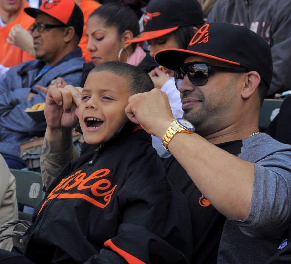 Jose Godoy of Miami pinches the ears of his son and a nephew of Manny Machado's, J.J. Godoy, 5 at the Baltimore Orioles' home opener at Oriole Park at Camden Yards. (Karl Merton Ferron/Baltimore Sun Staff)