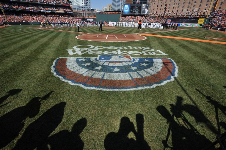 Photographers' shadows are seen during pre-game festivities before to the Orioles' home opener against the Minnesota Twins. (Gene Sweeney Jr./Baltimore Sun)