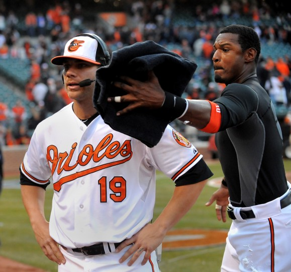 """Adam Jones races around Chris Davis to give him the now expected """"pie"""" during post game interview. Home opener for the Baltimore Orioles as they face the Minnesota Twins. (Gene Sweeney Jr./Baltimore Sun)"""