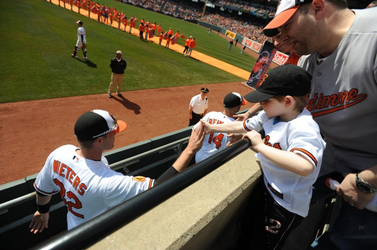 Coby Kreitzer (5) of Owings Mills gets a high five from Orioles' catcher Matt Weiters on opening day at Oriole Park at Camden Yards. (Jerry Jackson/Baltimore Sun)