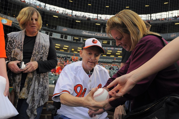 Trudy Zill watches her husband get a baseball while nurse Christa Herrick buttons his jersey so he can throw out the first pitch. (Karl Merton Ferron/Baltimore Sun)