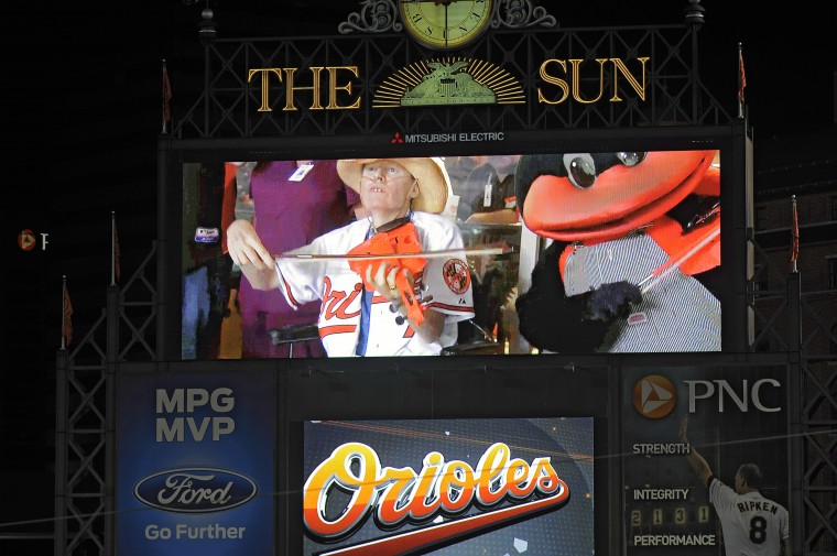 """Zill """"plays"""" orange fake fiddle on the video board"""