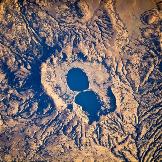 The Dendi Caldera is located on the Ethiopian Plateau, approximately 86 kilometers southwest of Addis Ababa. A caldera is a geological feature formed by the near-total eruption of magma from beneath a volcano. Two shallow lakes have formed within the central depression (image center). This image also highlights a radial drainage pattern surrounding the remnants of the Dendi volcanic cone. Radial drainage patterns commonly form around volcanoes, as rainfall can flow down slope on all sides of the cone and incise channels. NASA image