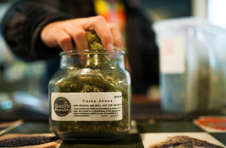 "An employee of Ganja Gourmet in Denver, Colorado, re-stocks ""top shelf"" medical marijuana in the business's retail space on April 17, 2013. (Dustin Bradford/MCT Photo)"