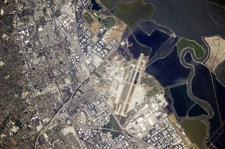 This astronaut photograph illustrates the diverse built environment surrounding the NASA Ames Research Center located at the southernmost end of San Francisco Bay. Founded in 1939 as an aircraft research laboratory, Ames became a NASA facility in 1958. Its original aircraft research focus was enhanced by the adjacent Moffett Field - an active Naval Air Station until 1994, and the original home of the Navy dirigible U.S.S. Macon. The large hanger for docking the U.S.S. Macon is still present at Moffett Field, and is visible in this astronaut photograph (image center). Today, NASA Ames includes the former Naval Air Station, and it continues its focus on aeronautics in addition to nanotechnology, information technology, fundamental space biology, biotechnology, thermal protection systems, and human factors research. NASA image