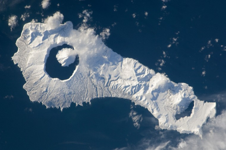 Snow cover highlights the calderas and volcanic cones that form the northern and southern ends of Onekotan Island, part of the Russian Federation in the western Pacific Ocean. Calderas are depressions formed when a volcano empties its magma chamber in an explosive eruption and then the overlaying material collapses into the evacuated space. In this astronaut photograph from the International Space Station, the northern end of the island (image right) is dominated by the Nemo Peak volcano, which began forming within an older caldera approximately 9,500 years ago. The last recorded eruption at Nemo Peak occurred in the early 18th century. NASA photo