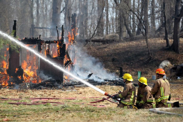 Howard County Fire Department trainees work with an instructor during a controlled burn on Weavers Court in Ellicott City, MD on Tuesday, April 9, 2013. (Jen Rynda/Patuxent Publishing)