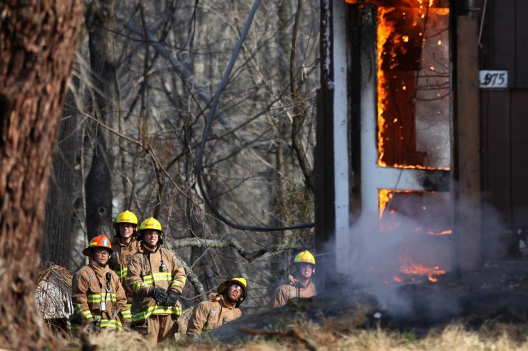 Howard County Fire Department trainees watch to see how a fire makes its way through a house during a controlled burn on Weavers Court in Ellicott City, MD on April 9, 2013. (Jen Rynda/Patuxent Publishing)