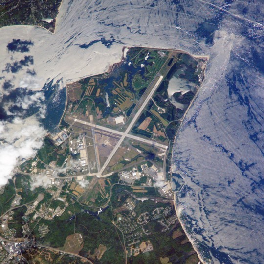 """Maryland's Patuxent River Naval Air Station is located on a small peninsula, bordered by the Patuxent River to the north-northeast and Chesapeake Bay to the east and southeast. The air station was commissioned in 1943, replacing farmlands that had occupied the peninsula less than a year earlier. The primary purpose of """"Pax River"""" (as the site is known by the U.S. Navy) was to consolidate geographically dispersed testing facilities that existed prior to World War II. The Patuxent River station is now the primary center for naval air technology research, development, testing, and support, as well as being the location of the Navy Test Pilot School. International Space Station crews frequently use the Patuxent River Naval Air Station as a geographic reference point and photographic training target. This astronaut photograph illustrates why, the distinctive pattern of the airfield runways and the station's location in Chesapeake Bay make it easy to spot from orbit. The sharp boundaries between different kinds of land surfaces are good for camera focusing practice. NASA image"""