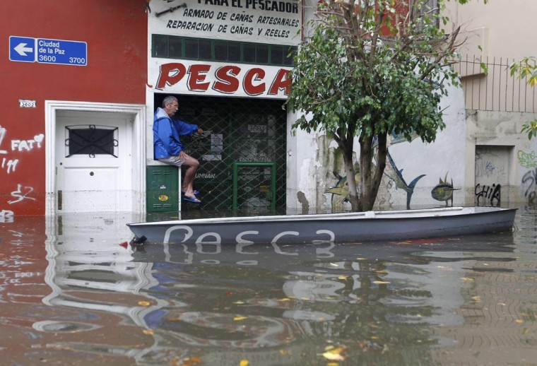 A man is seen next to a boat in a flooded street after a rainstorm in Buenos Aires April 2, 2013. Thunderstorms damaged property and vehicles, cut power and caused delays on flights in Buenos Aires and its suburbs. The City's SAME emergency service announced that the death toll has risen to five. (Enrique Marcarian/Reuters)