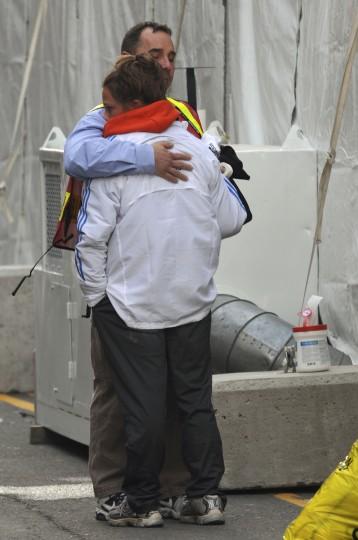 """Members of the Boston Marathon medical team embrace after treating victims of explosions near the finish line of the Boston Marathon in Boston, Massachusetts April 15, 2013. Two bombs ripped through the crowd at the finish line of the Boston Marathon on Monday, killing three people, maiming others and injuring more than 100 in what a White House official said would be treated as an """"act of terror."""" (Neal Hamberg/Reuters photo)"""