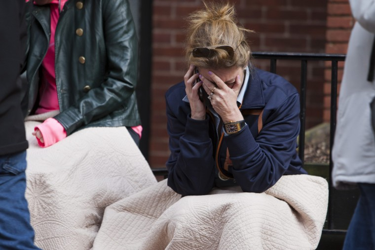 """A woman talks on the phone after two explosions interrupted the running of the Boston Marathon in Boston, Massachusetts April 15, 2013. Two bombs ripped through the crowd at the finish line of the Boston Marathon on Monday, killing two people and injuring dozens in what a White House official said would be handled as an """"act of terror."""" (Dominick Reuter/Reuters photo)"""