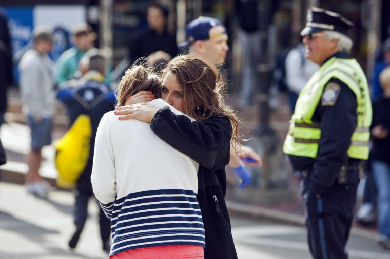 A woman comforts another, who appears to have suffered an injury to her hand, after explosions interrupted the 117th Boston Marathon in Boston, Massachusetts April 15, 2013. Two people were killed and 23 others injured after two explosions struck the Boston Marathon as runners crossed the finish line on Monday, Boston police said. (Dominick Reuter/Reuters photo)