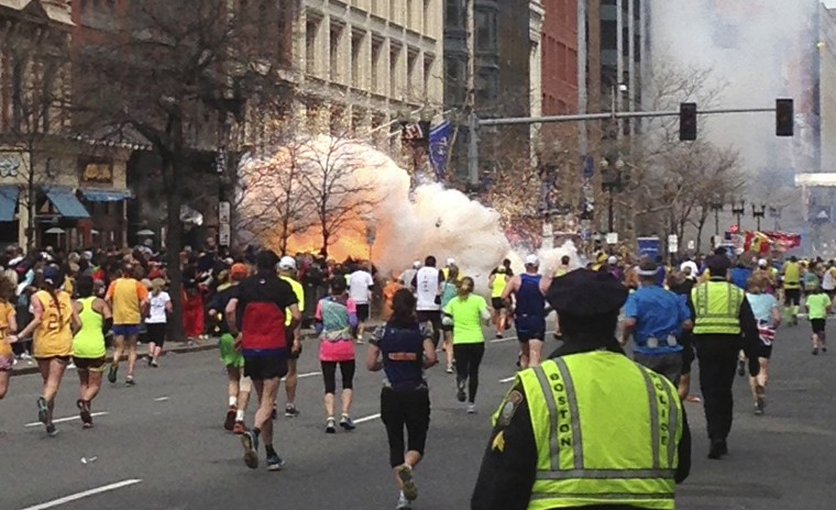 Runners continue to run towards the finish line of the Boston Marathon as an explosion erupts near the finish line of the race in Boston, Massachusetts, April 15, 2013. Two simultaneous explosions ripped through the crowd at the finish line of the Boston Marathon on Monday, killing at least two people and injuring dozens on a day when tens of thousands of people pack the streets to watch the world famous race. (Dan Lampariello/Reuters photo)