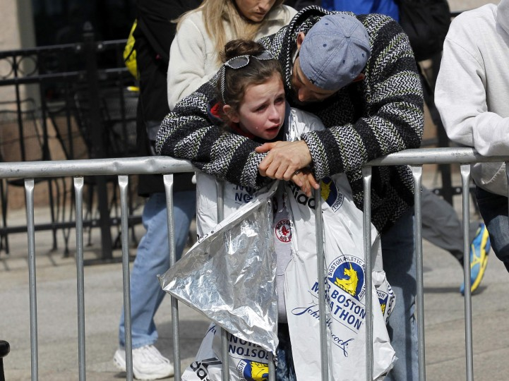 A child is comforted after explosions went off at the 117th Boston Marathon in Boston, Massachusetts April 15, 2013. Two explosions hit the Boston Marathon as runners crossed the finish line on Monday, killing at least two people and injuring 23 on a day when tens of thousands of people pack the streets to watch one of the world's best known marathons. (Jessica Rinaldi/Reuters photo)