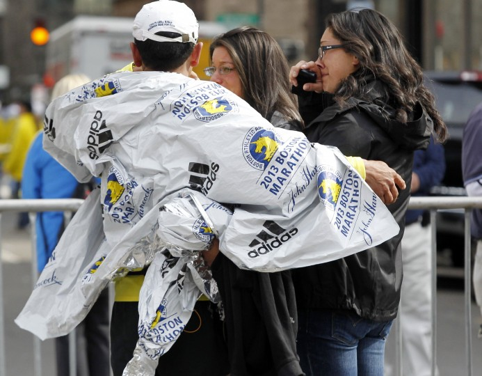 People comfort each other after explosions went off at the 117th Boston Marathon in Boston, Massachusetts April 15, 2013. Two explosions hit the Boston Marathon as runners crossed the finish line on Monday, killing at least two people and injuring 23 on a day when tens of thousands of people pack the streets to watch one of the world's best known marathons. (Jessica Rinaldi/Reuters photo)