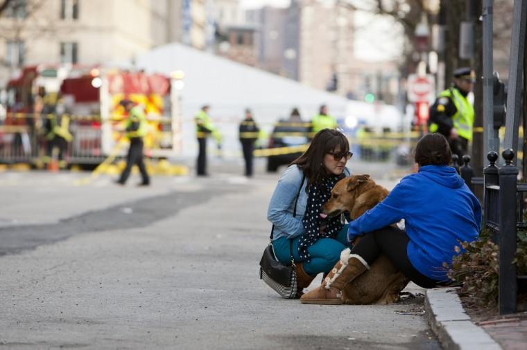 """Two women sit with their dog near the scene after two explosions interrupted the running of the Boston Marathon in Boston, Massachusetts April 15, 2013. Two bombs ripped through the crowd at the finish line of the Boston Marathon on Monday, killing two people and injuring dozens in what a White House official said would be handled as an """"act of terror."""" (Dominick Reuter/Reuters photo)"""