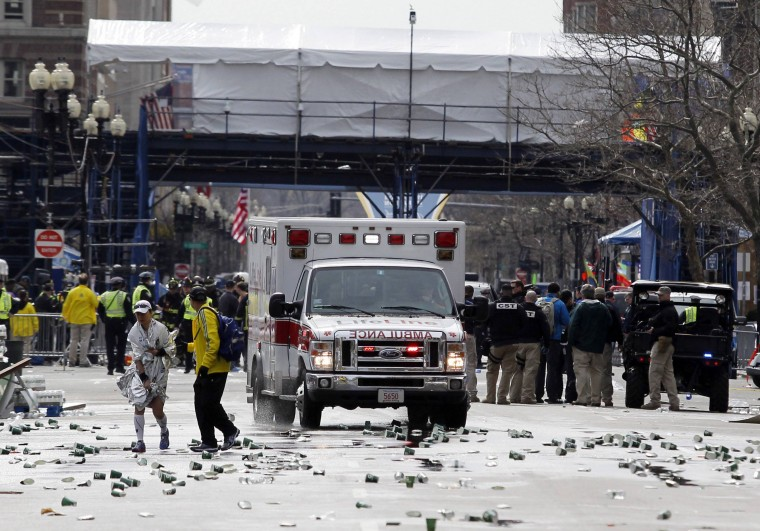 A runner is escorted from the scene after explosions went off at the 117th Boston Marathon in Boston, Massachusetts April 15, 2013. Two explosions hit the Boston Marathon as runners crossed the finish line on Monday, killing at least two people and injuring 23 on a day when tens of thousands of people pack the streets to watch one of the world's best known marathons.(Jessica Rinaldi/Reuters photo)