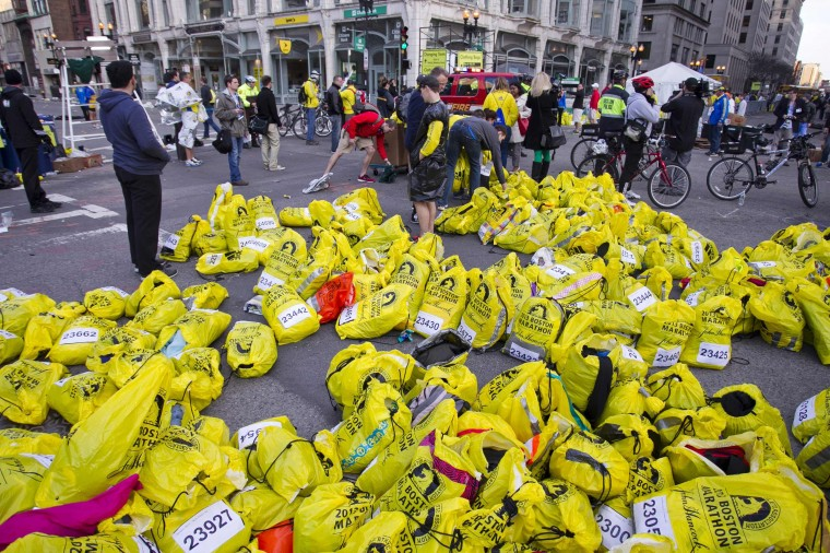 """Volunteers organize participants for belongings for collection after two explosions interrupted the running of the Boston Marathon in Boston, Massachusetts April 15, 2013. Two bombs ripped through the crowd at the finish line of the Boston Marathon on Monday, killing two people and injuring dozens in what a White House official said would be handled as an """"act of terror."""" (Dominick Reuter/Reuters photo)"""