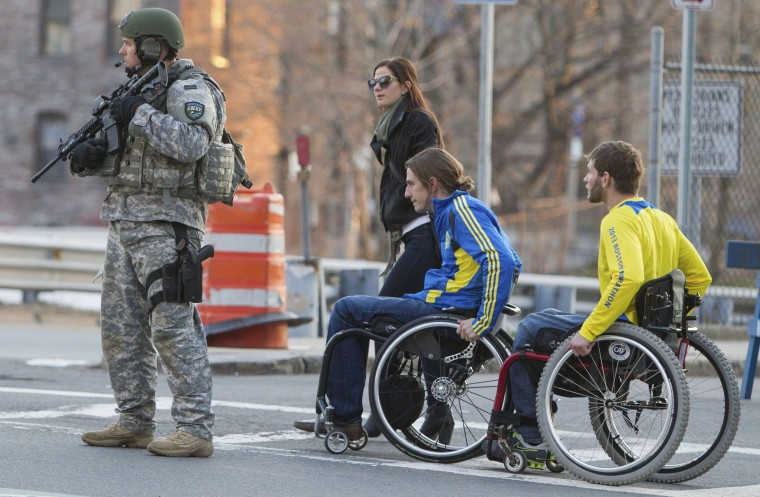 """A metro SWAT officer stands guard on Massachusetts Avenue near the scene of multiple bombings near the finish line of the Boston Marathon in Boston, Massachusetts April 15, 2013. Two bombs ripped through the crowd at the finish line of the marathon on Monday, killing three people, and injuring more than 100 in what the a White House official said would be handled as an """"act of terror"""". (Scott Eisen/Reuters photo)"""