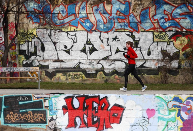 A jogger runs past graffiti on a sunny spring day in Vienna April 4, 2013. (Heinz-Peter Bader/Reuters photo)