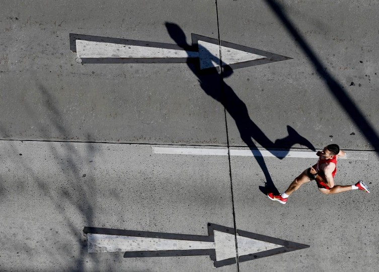 A runner casts a shadow as he takes part in the Vienna City Marathon in Vienna April 14, 2013. (Leonhard Foeger/Reuters)