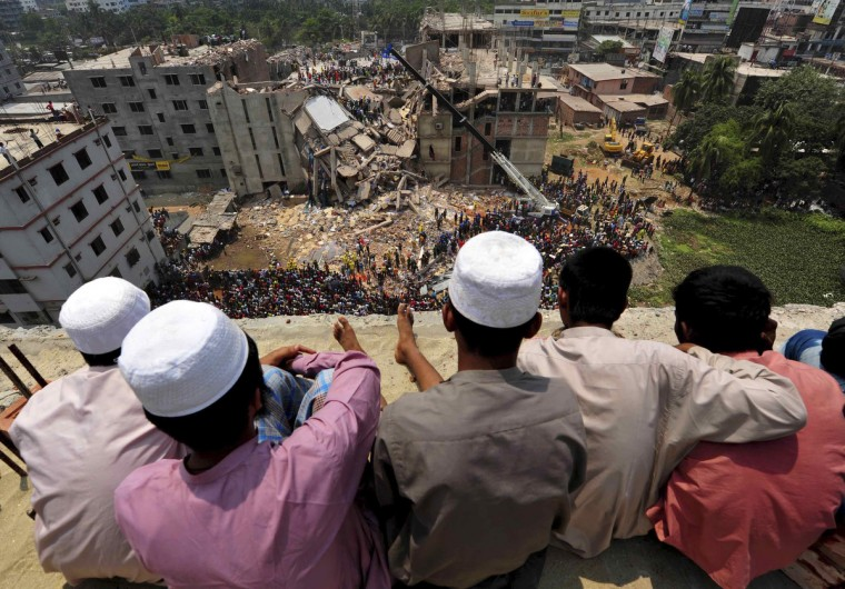People watch as rescue workers continue their operations at the collapsed Rana Plaza building in Savar, 30 km (19 miles) outside Dhaka. Survivors from the garment factory that collapsed in Bangladesh killing at least 228 people described on Thursday a deafening bang and tremors before the eight-floor building crashed down under them. (Reuters photo)