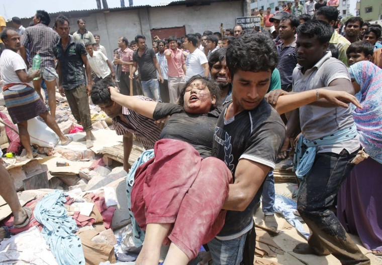 People rescue a garment worker who was trapped under the rubble of the collapsed Rana Plaza building in Savar, 19 miles outside Dhaka April 24, 2013. The eight-storey block housing factories and a shopping centre collapsed on the outskirts of the Bangladeshi capital on Wednesday, a government official said. (Andrew Biraj/Reuters)