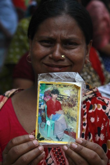 A relative holds a picture of a missing garment worker, who was working in the Rana Plaza building when it collapsed, in Savar, 19 miles outside Dhaka April 24, 2013. The eight-storey block housing factories and a shopping centre collapsed on the outskirts of the Bangladeshi capital on Wednesday, a government official said. (Andrew Biraj/Reuters)