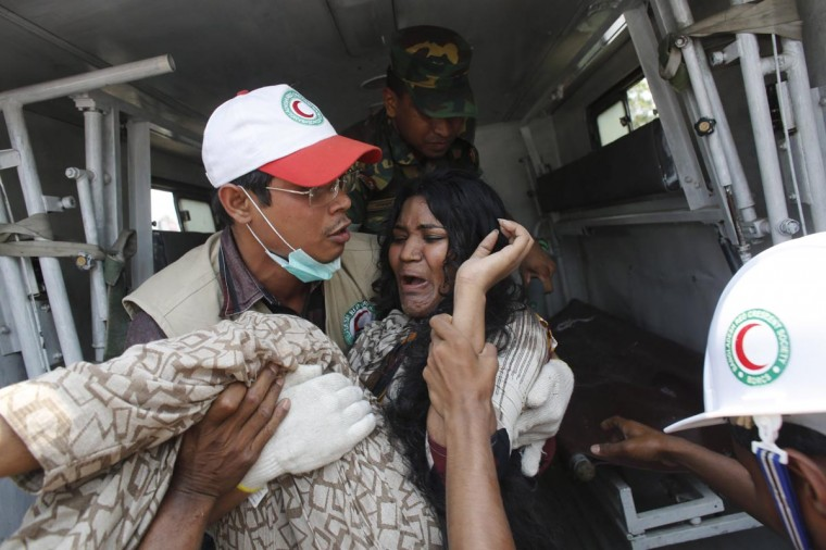 A rescue worker carries a garment worker to an ambulance after pulling her from the rubble of the collapsed Rana Plaza building in Savar, 19 miles outside Dhaka April 24, 2013. The eight-storey block housing factories and a shopping centre collapsed on the outskirts of the Bangladeshi capital on Wednesday, a government official said. (Andrew Biraj/Reuters)
