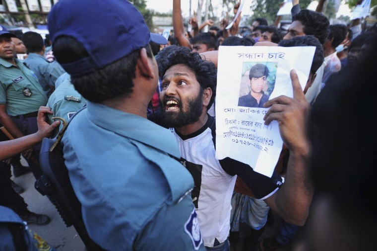 A relative argues with a member of the police as he shows a picture of a garment worker, who has been missing, during a protest demanding capital punishment for those responsible for the collapse of the Rana Plaza building in Savar, outside Dhaka April 29, 2013. Rescue officials in Bangladesh said on Monday they were unlikely to find more survivors in the rubble of a factory building that collapsed last week burying hundreds of garment workers in the country's worst industrial accident. (Khurshed Rinku/Reuters)