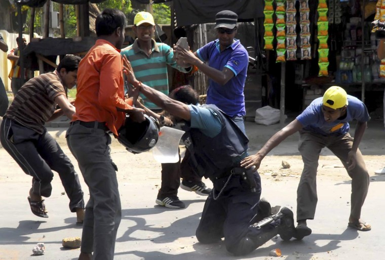 Jamaat-e-Islami activists smash pieces of bricks on the head of Jahangir Alam, officer in-charge of Upashahar police camp, and try to snatch his pistol during a clash in Rajshahi April 1, 2013. At least four policemen were injured, one critically, and a firearm and a walkie-talkie were snatched from them when Jamaat-e-Islami activists and its student wing Islami Chhatra Shibir clashed with police in Rajshahi city on Monday morning, local media reported. (Stringer/Reuters)