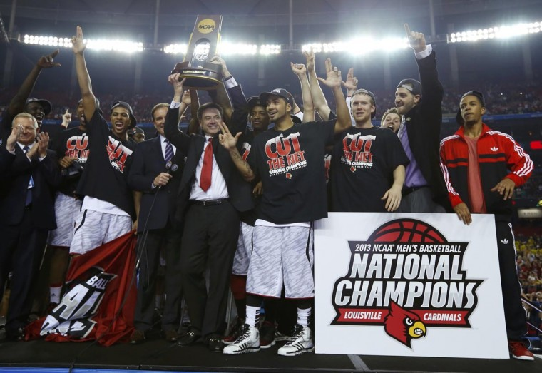 Louisville Cardinals head coach Rick Pitino holds up the trophy as he and his team celebrate after defeating the Michigan Wolverines in their NCAA men's Final Four championship basketball game in Atlanta, Georgia April 8, 2013. (Jeff Haynes/Reuters)