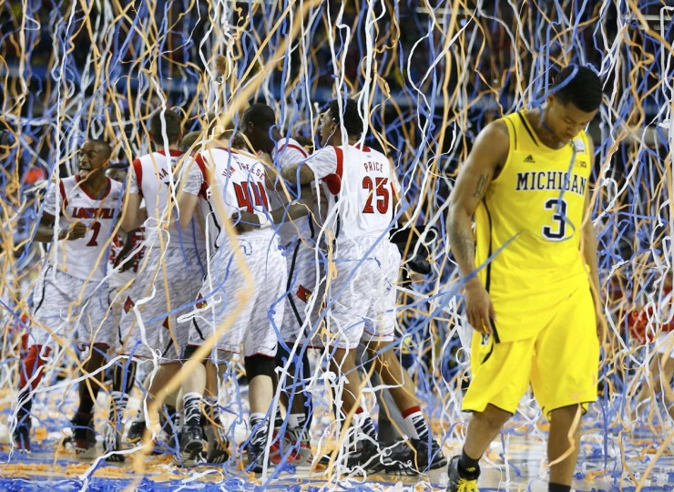 Michigan Wolverines guard Trey Burke (3) walks off the court as the Louisville Cardinals celebrate defeating Michigan to win the NCAA men's Final Four championship basketball game in Atlanta, Georgia April 8, 2013. (Jeff Haynes/Reuters)