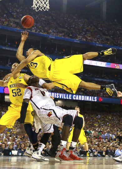 Michigan Wolverines guard Trey Burke (3) tries to score over top of Louisville Cardinals center Gorgui Dieng (10) in the second half of their NCAA men's Final Four championship basketball game in Atlanta, Georgia April 8, 2013. (Jeff Haynes/Reuters)