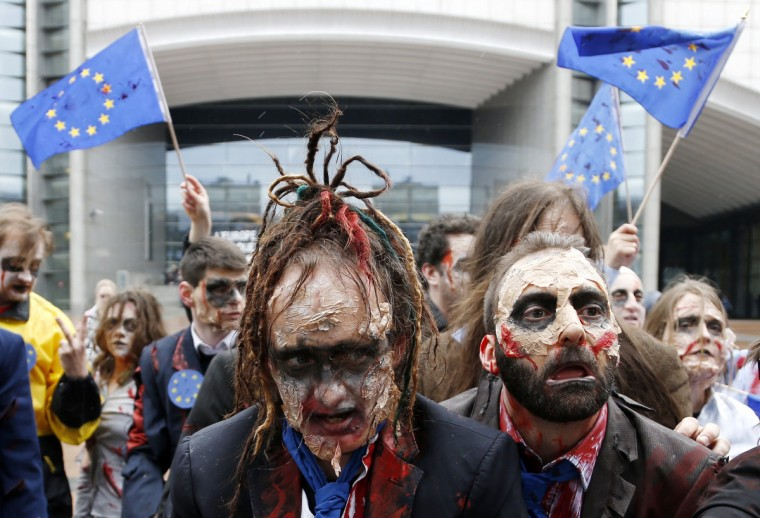 """Demonstrators, including members of the European Parliament (MEP), dressed as zombies, dance to the music of Michael Jackson's """"Thriller"""" while participating in a flash-mob in front of the EU Parliament in Brussels. The flash-mob was organized in protest against possible EU-India free trade agreements that could endanger access to medicines, organisers said. (Francois Lenoir/Reuters)"""