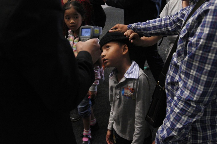 An airport security personnel takes a body temperature reading of a boy as he arrives at Hong Kong International Airport. A strain of bird flu that has been found in humans for the first time in eastern China is no cause for panic, the World Health Organization said on Monday, as the number of people infected rose to 24, with seven deaths. (Tyrone Siu/Reuters)
