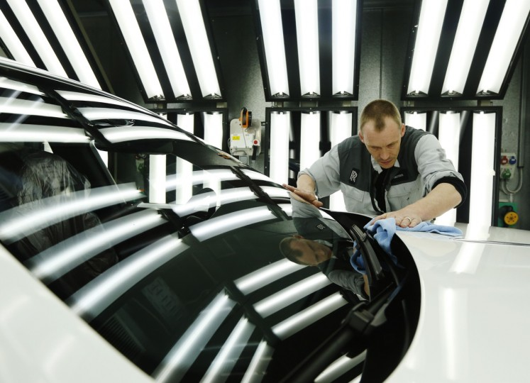 Employee Darren Lowarson give a Rolls Royce Ghost its final finish polish at the Rolls Royce Motor Cars factory at Goodwood near Chichester in southern England. Britain's economy dodged a return to recession and grew faster than expected in the first three months of this year, a relief for finance minister George Osborne. (Luke MacGregor/Reuters photo)