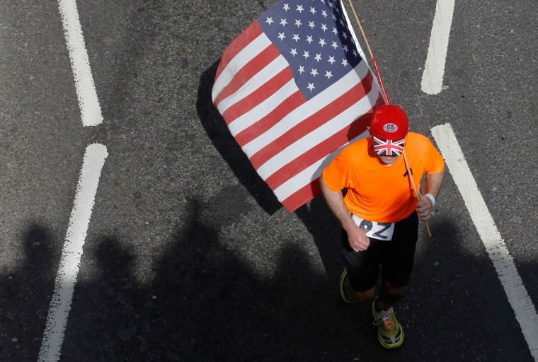 A runner carrying a U.S. flag passes the shadows of spectators cast on the Embankment during the London Marathon. (Luke MacGregor/Reuters)