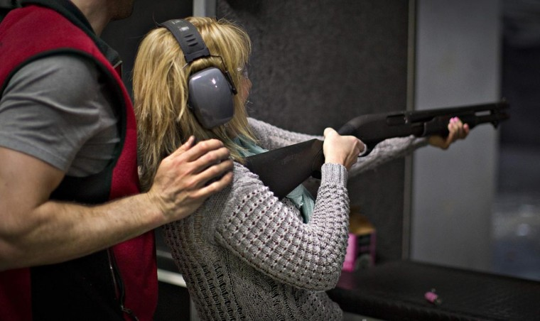 A range officer prevents a woman from falling back while she fires a shotgun at the DVC Indoor Shooting Centre in Port Coquitlam, British Columbia March 22, 2013. (Andy Clark/Reuters)