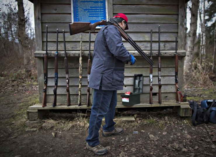 "A member of the Vancouver Gun Club gets more ammunition while taking part in sporting clays at their facility in Richmond, British Columbia February 17, 2013. Sporting clays, also known as ""golf with a shotgun"", uses clay targets to simulate various birds and projects the targets in different directions and heights. (Andy Clark/Reuters)"