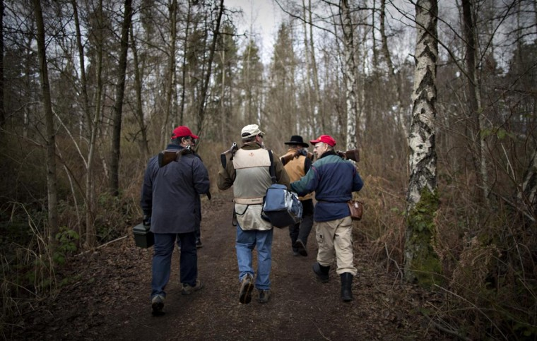 Shooters, taking part in sporting clays, walk through a wooded area to their next position at the Vancouver Gun Club in Richmond, British Columbia February 17, 2013. (Andy Clark/Reuters)