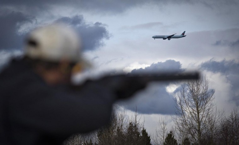 An aeroplane flies over as a member of the Vancouver Gun Club partakes in trapshooting in Richmond, British Columbia February 17, 2013. (Andy Clark/Reuters)