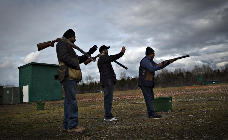Shooters check the angle while waiting for their turn during skeet shooting at the Vancouver Gun Club in Richmond, British Columbia February 17, 2013. (Andy Clark/Reuters)
