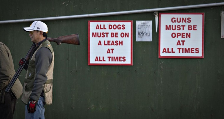 A man rests a shotgun on his shoulder next to signs posted on a wall at the Vancouver Gun Club in Richmond, British Columbia February 10, 2013. (Andy Clark/Reuters)