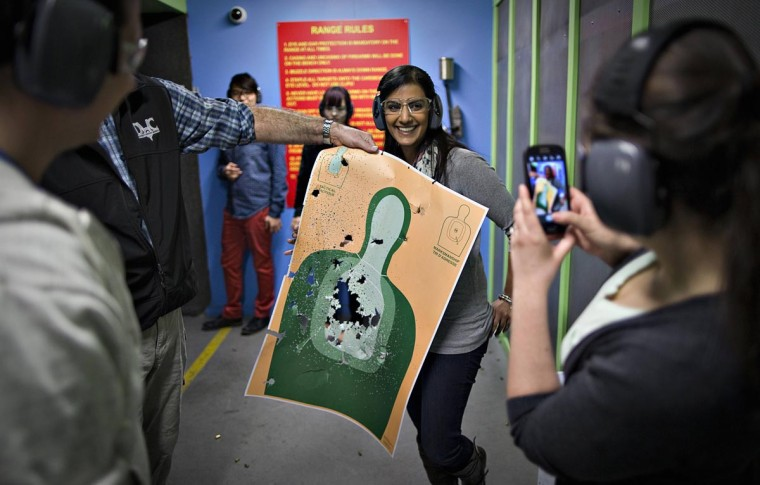 Mona Kambo (C) holds up her shooting target while her friend Kylie Cronin (R) takes a picture at the DVC Indoor Shooting Centre in Port Coquitlam, British Columbia March 22, 2013. Canada has very strict laws controlling the use of handguns and violent crime is relatively rare. (Andy Clark/Reuters)